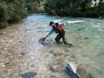 pêcheur à la mouche avec des cuissardes dans l'eau