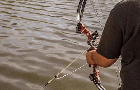 Bowfisher visant son arc sur l'eau