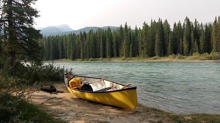 canoë avec des sacs garés au bord de la rivière