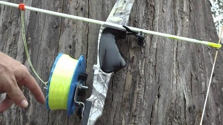 doigt pointé sur une bobine attachée à un arc sur bois