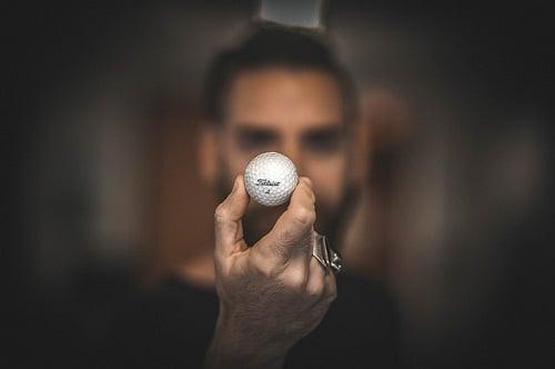 main concentrée tenant une balle de golf