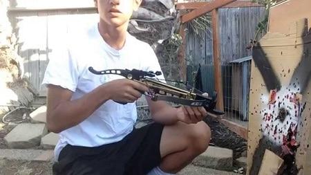 Kid tenant une arbalète de pistolet à côté de la cible