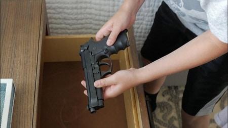 enfant tenant un pistolet dans le tiroir