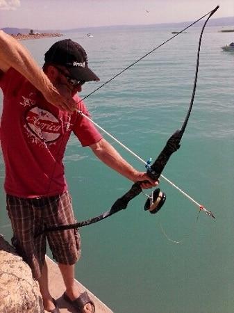 Bowfishing homme avec recurve sur une falaise au bord de la plage