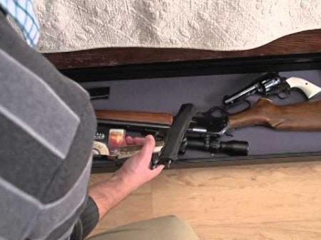 homme obtenant un pistolet de coffre-fort sous le lit