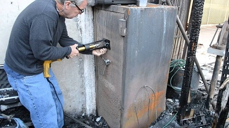 Homme ouvrant un coffre-fort après un incendie