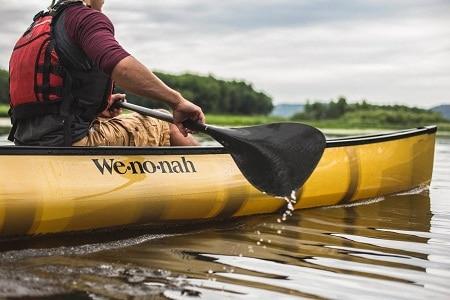 Homme pagayer en canoë sur l'eau encore