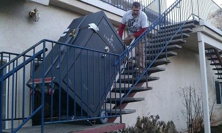 homme tirant un coffre-fort dans les escaliers
