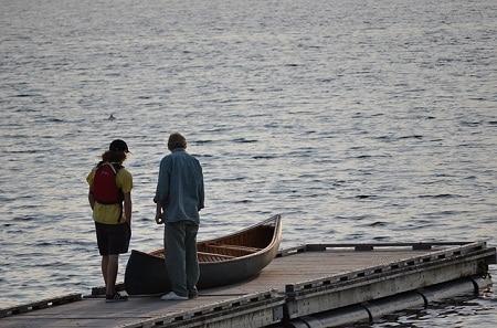 hommes debout à côté de canoë