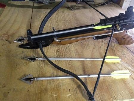 Arbalète pistolet à tirage complet sur la table avec des flèches