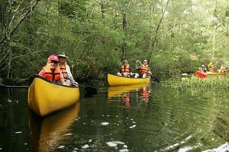 touristes pagayant des canoës sur une rivière