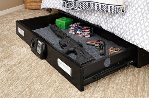 sous le coffre-fort de pistolet de lit avec des fusils et des balles