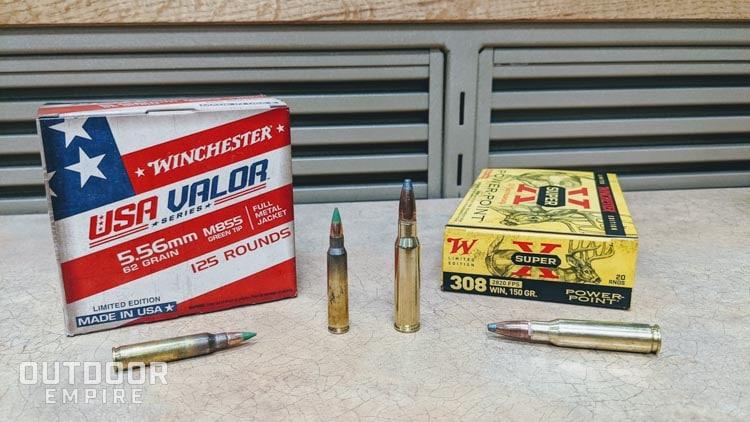 Boîte de munitions 5,56 mm à côté d'une boîte de munitions .308 avec quelques cartouches à l'avant