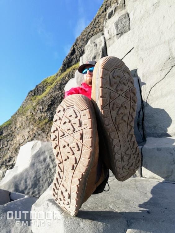 Assis sur des rochers avec les jambes croisées et le bas des bottes Kodiak Skogan montrant