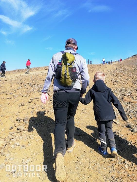 Vue de derrière de papa randonnée en bottes Kodiak Skogan avec son fils